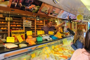 a cheese vendor in the albert cuyp market hands an eager customer her treats