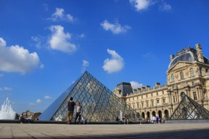 the louvre graciously poses for a pic on a blue sky day in paris